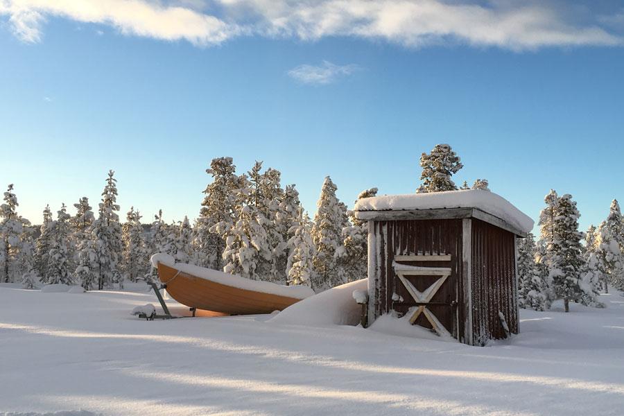 Schweden-Kiruna-Schuppen am See im Winter
